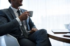 Businessman having coffee in office lobby Royalty Free Stock Images