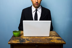 Businessman having coffee and working on laptop Stock Image