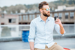 Businessman having a coffeebreak on the rooftop. Handsome businessman having a coffeebreak on the rooftop on the industrial background stock photos