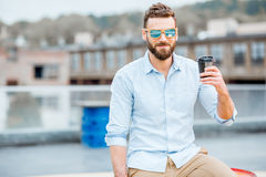Businessman having a coffeebreak on the rooftop. Handsome businessman having a coffeebreak on the rooftop on the industrial background royalty free stock photo