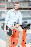 Businessman having a coffeebreak on the rooftop. Handsome businessman having a coffeebreak sitting with skateboard on the rooftop on the industrial background stock images