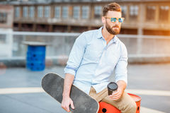 Businessman having a coffeebreak on the rooftop. Handsome businessman having a coffeebreak sitting with skateboard on the rooftop on the industrial background royalty free stock images