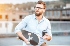 Businessman having a coffeebreak on the rooftop. Handsome businessman having a coffeebreak sitting with skateboard on the rooftop on the industrial background stock image