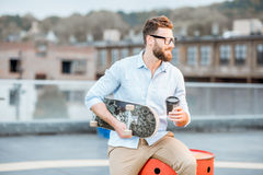 Businessman having a coffeebreak on the rooftop. Handsome businessman having a coffeebreak sitting with skateboard on the rooftop on the industrial background royalty free stock photo