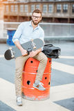 Businessman having a coffeebreak on the rooftop. Handsome businessman having a coffeebreak sitting with skateboard on the rooftop on the industrial background stock photography