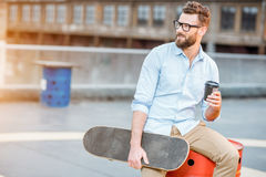 Businessman having a coffeebreak on the rooftop. Handsome businessman having a coffeebreak sitting with skateboard on the rooftop on the industrial background royalty free stock photography