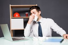 Businessman having cold in the head and sitting at workplace office royalty free stock photos