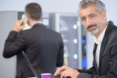 Businessman having cup coffe while working on laptop Royalty Free Stock Images