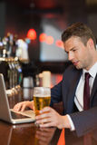 Businessman having a drink while working on his laptop Royalty Free Stock Images