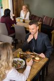 Businessman Having Food With Female Colleague Royalty Free Stock Photography