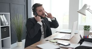Businessman singing and listening music at work. Businessman having fun singing and listening music through headphones at workplace stock video footage