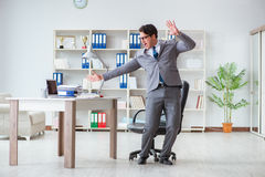The businessman having fun taking a break in the office at work. Businessman having fun taking a break in the office at work royalty free stock photo