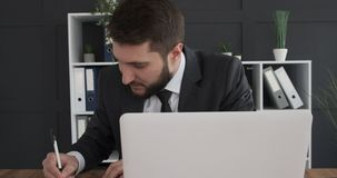 Businessman having a great idea at work. Thoughtful businessman having a great idea while using laptop and taking notes at office stock footage