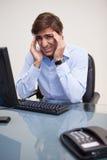 Businessman having a headache in his office Stock Photos