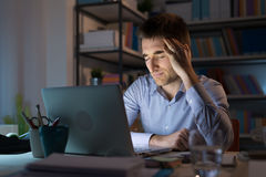Businessman having an headache. Businessman in the office working late at night and having a bad headache, overwork and stress concept Royalty Free Stock Image