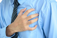 Businessman having heartache. Businessman having heart attack (heartache) with hand on chest Royalty Free Stock Photography
