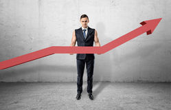 Businessman having muscular arms and holding big red line graph with an upturned arrow Royalty Free Stock Photo