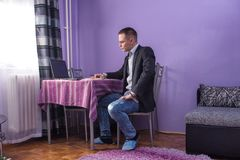 Working from home. Businessman is having a online meeting from his living room. Looking seriouse and werring top part of suite Stock Photography