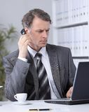 Businessman having phone call conversation at workplace Royalty Free Stock Image