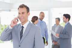 Businessman having phone call while his colleagues discussing Royalty Free Stock Photos