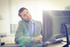 Businessman having phone call while using his computer Royalty Free Stock Image