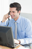 Businessman having phone call while using his laptop Stock Photography
