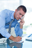 Businessman having a phone call and writing notes Stock Photography