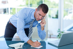Businessman having a phone call and writing notes Royalty Free Stock Photo