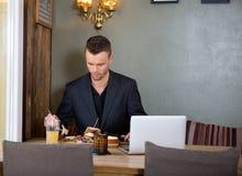 Businessman Having Sandwich At Restaurant Royalty Free Stock Photography