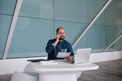Businessman having serious conversation on cell telephone while sitting in front of open net-book with paper documents in hand, Stock Photos