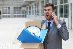 Businessman having a tantrum on the phone after being fired.  stock photo