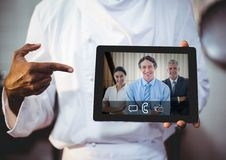 Businessman having video call with colleagues on digital tablet. Mid section of businessman having video call with colleagues on digital tablet Royalty Free Stock Photos