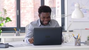 Businessman having video chat on laptop at office. Business, technology and communication concept - happy smiling african american businessman having video chat stock video footage