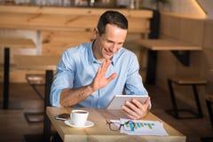 Businessman having videochat using digital tablet. Smiling businessman sitting in cafe, having videochat using digital tablet and waving on the camera stock images