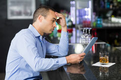 Businessman having a whisky and using laptop Royalty Free Stock Images