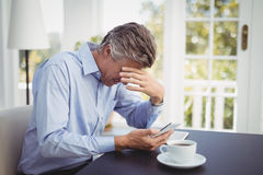 Businessman with head in hand in restaurant. Depressed businessman with head in hand in restaurant Stock Images