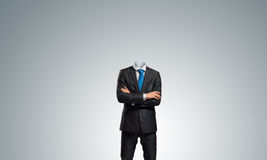 Businessman without head. Headless businessman with arms crossed on chest in black suit stock image