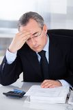 Businessman With Headache In Office. Mature Businessman Having Headache Sitting At Desk In Office Royalty Free Stock Photos