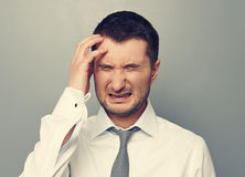 Businessman with headache over grey background Royalty Free Stock Photography