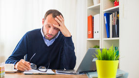 Businessman with headache sitting in his office. Stock Photo