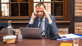Businessman with headache sitting in restaurant. Stock Photography