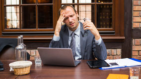 Businessman with headache sitting in restaurant. Royalty Free Stock Image