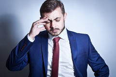 Businessman with a headache. Standing with his hand on his brow Royalty Free Stock Images