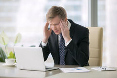 Businessman with headache. Young shocked businessman sitting with laptop at desk, having headache, poor cash flow, balance, low profit, unable to deal with fears royalty free stock image