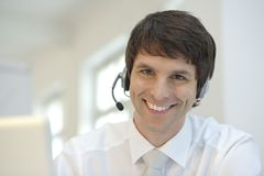 Businessman with headphones. Smiling and working on his laptop stock photos