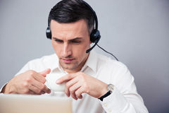 Businessman in headphones drinking coffee Royalty Free Stock Photo