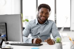 Businessman with headphones and papers at office. Business, technology and people concept - happy african american businessman with headphones and papers Royalty Free Stock Images
