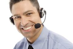 Businessman with headset. Businessman smiles as he uses a headset Royalty Free Stock Image