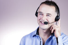 Businessman with a headset calling cheerfully. Royalty Free Stock Photography