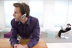 Businessman with headset, colleague in background Royalty Free Stock Photo